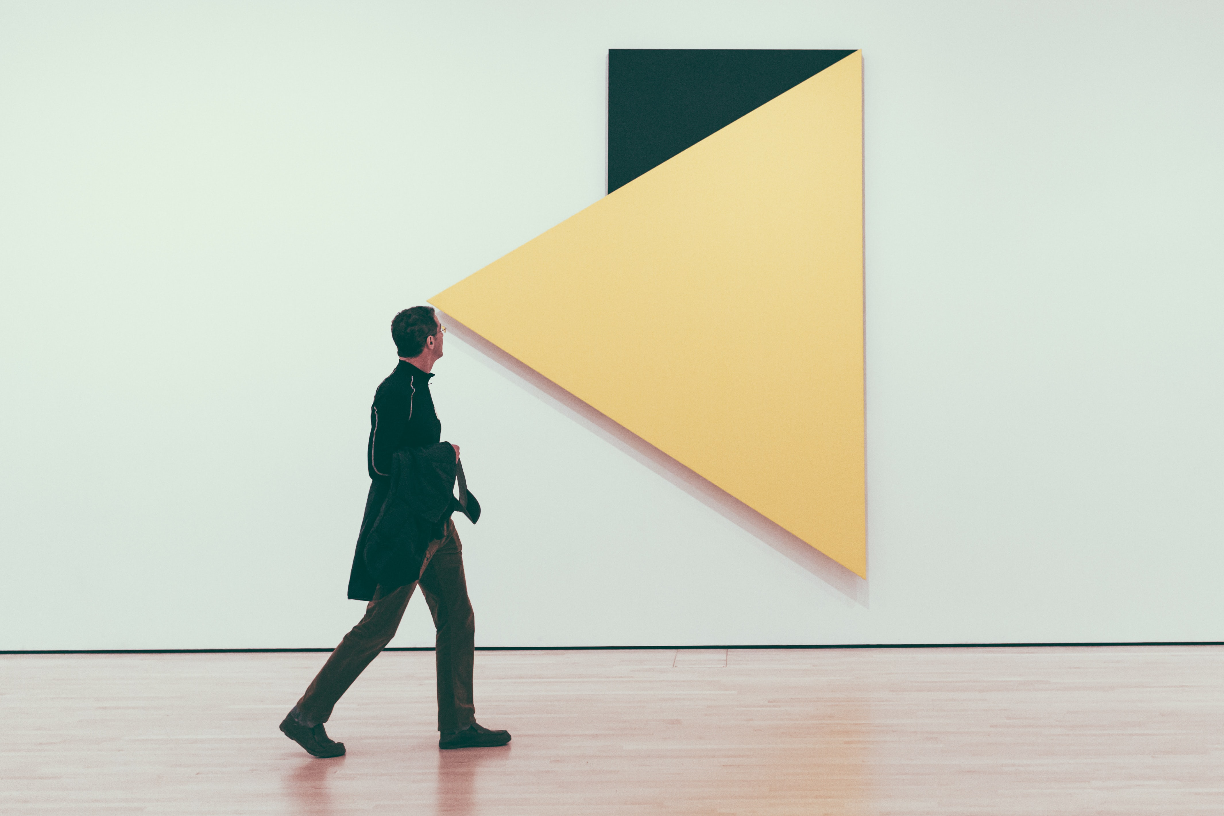 man looking on inverted yellow and green triangle wall art