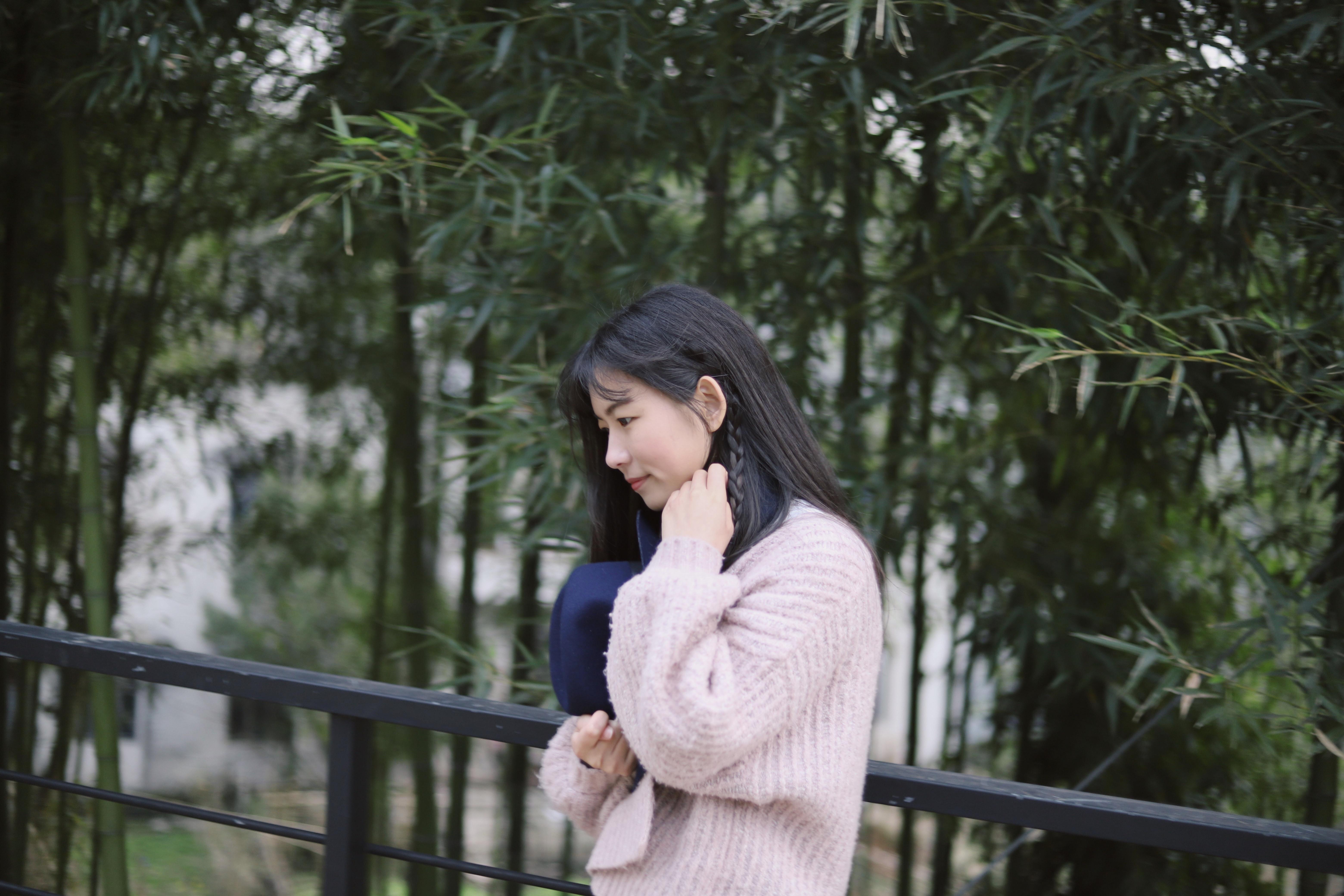 woman in pink sweatshirt standing near fence