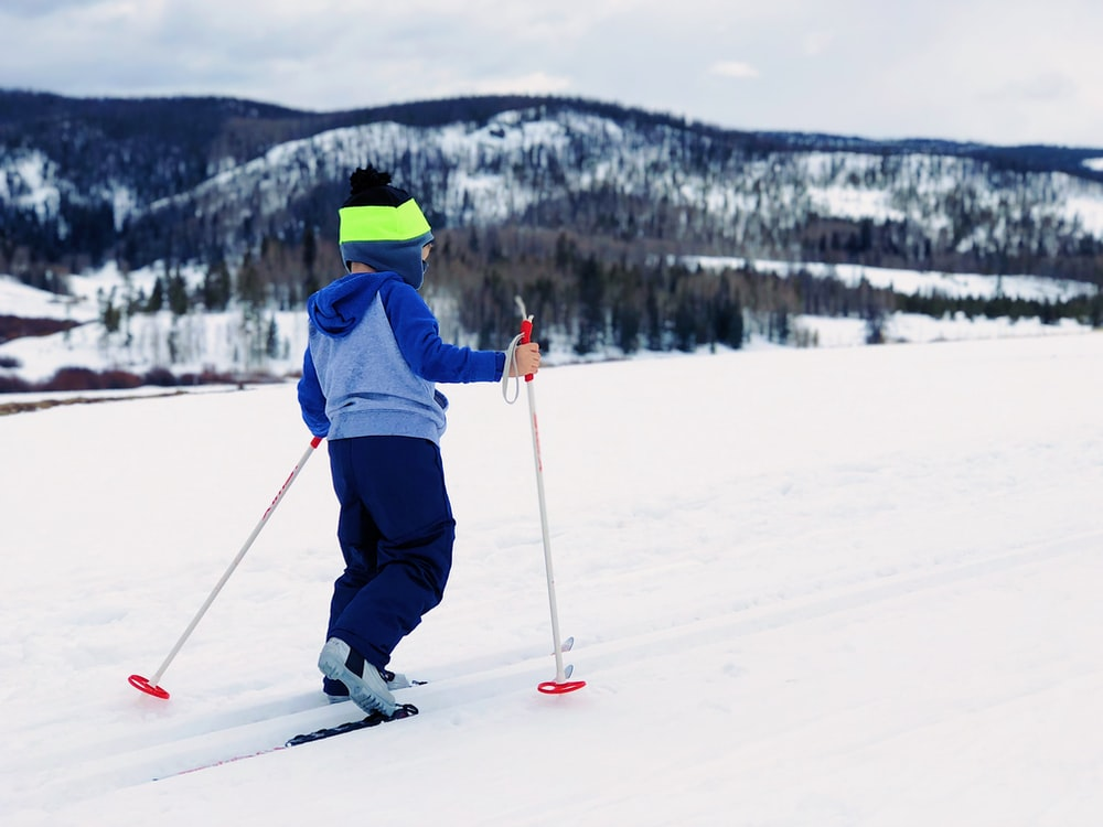 boy in blue and gray hoodie doing snow ski