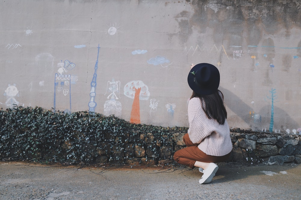 woman kneeling near gray concrete wall with full of drawings