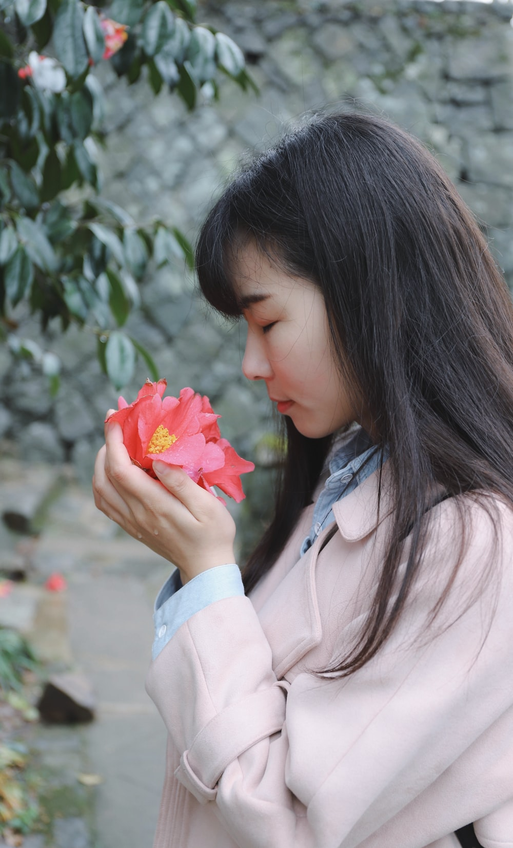 woman sniffing flower on her hands