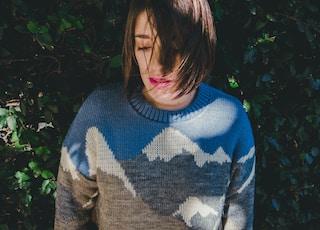 woman wearing sweater near green grass wall