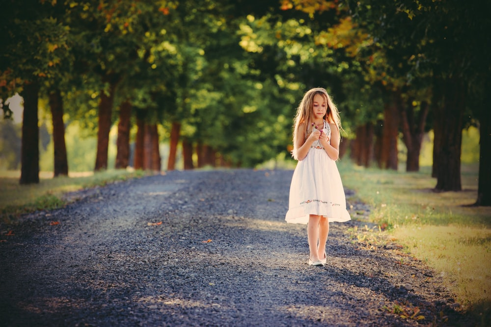 girl standing between green leafed trees