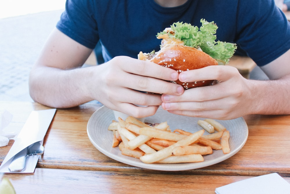 person eating hamburger with fries on plate