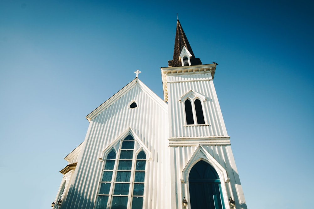 worm's-eye view photography of white and brown church