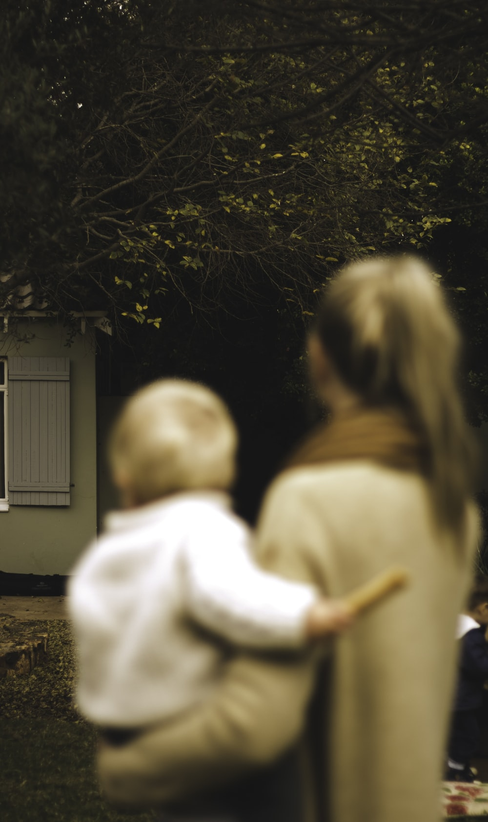 shallow focus photography of woman carrying baby in front of house