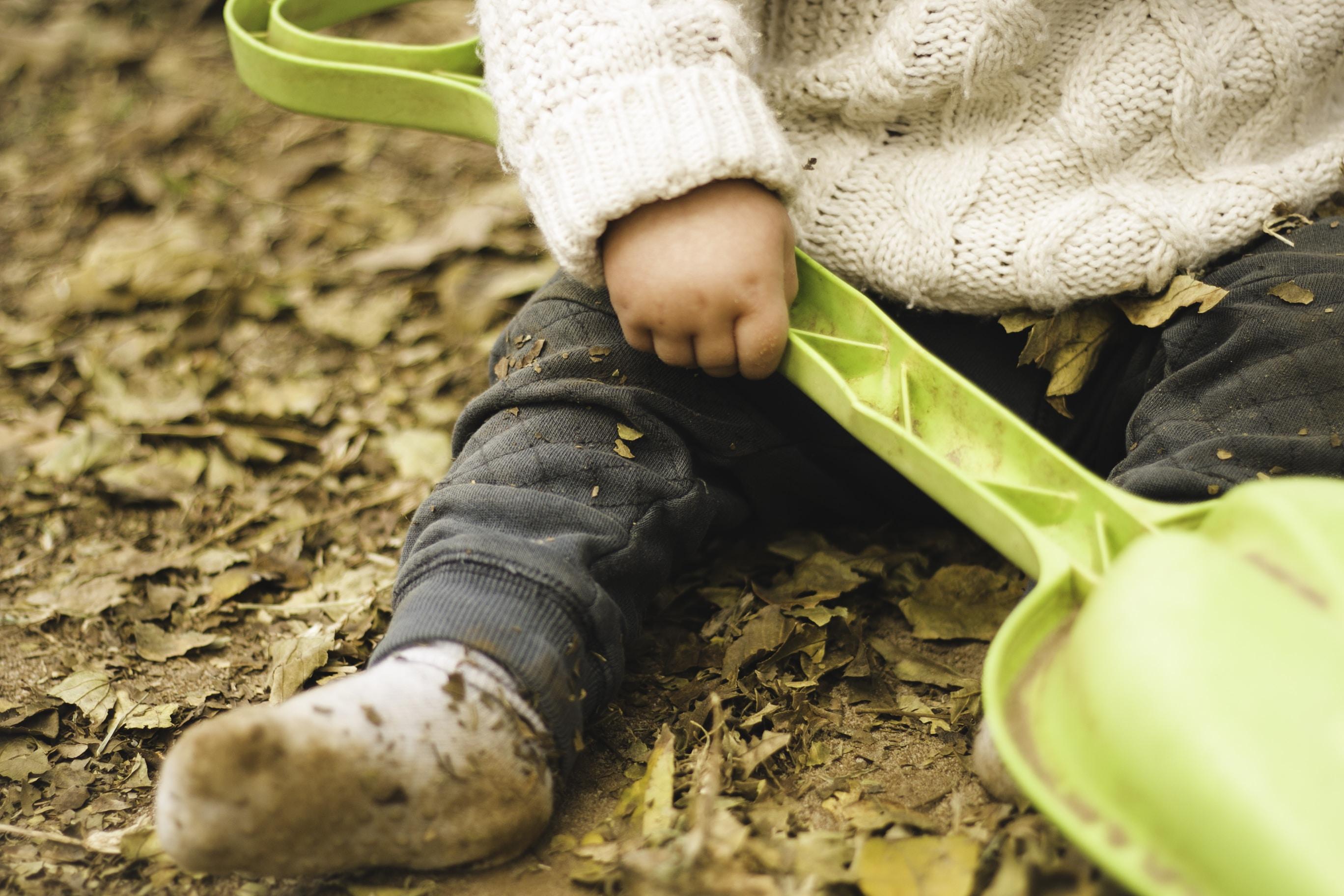 child holding green plastic shovel toy