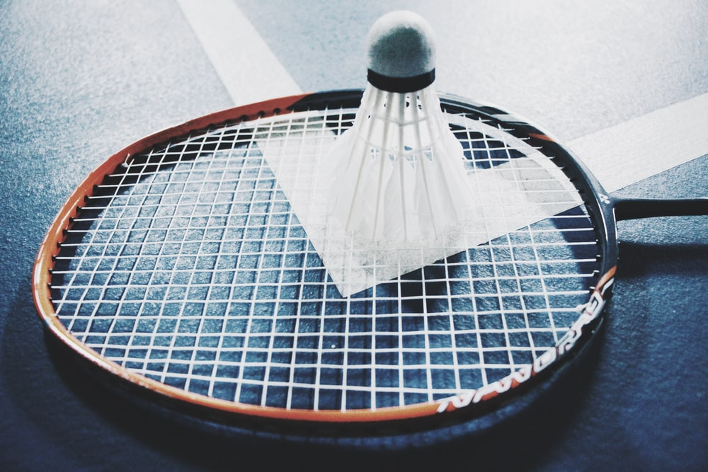 white shuttlecock on brown and black badminton racket placed on floor