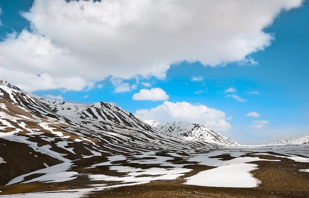 snowy mountain under white clouds