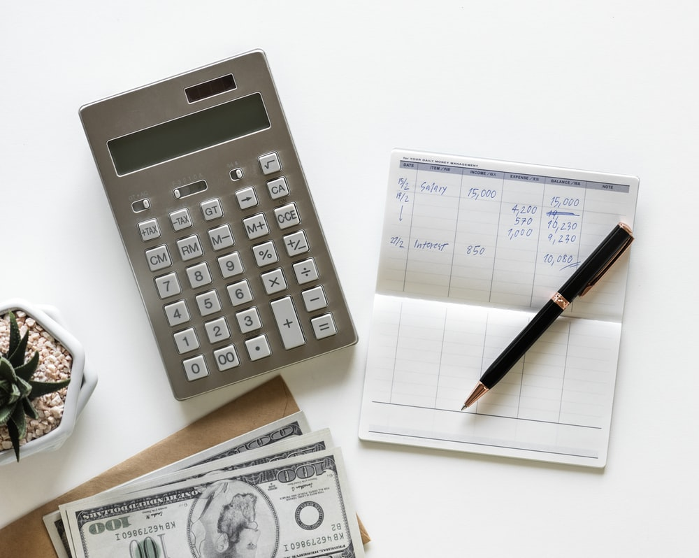 flatlay photography of calculator between stack of banknote and click pen