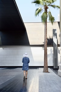 woman walking near palm tree and concrete building at daytime