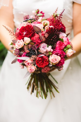 a bride holding a beautiful hand-tied wedding bouquet