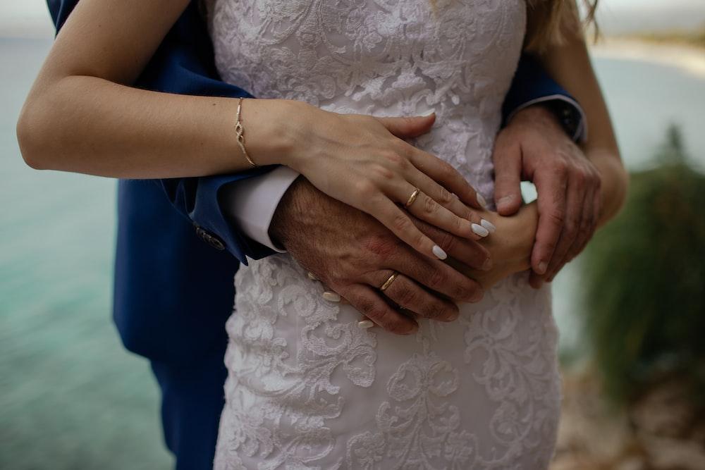 man wrapping hand around woman's waist