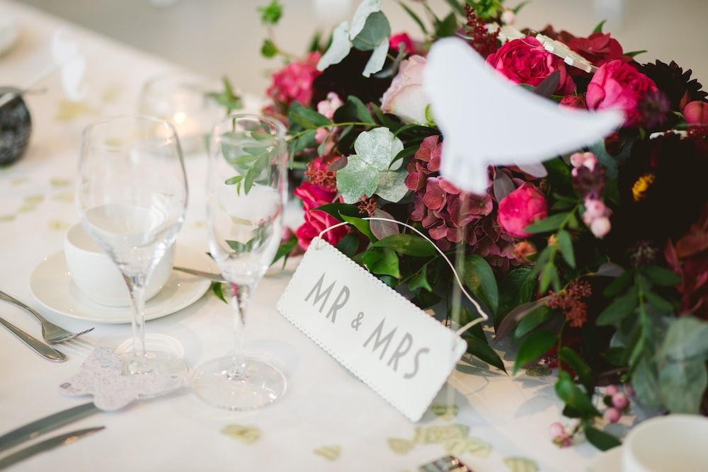 two wine glasses near flower arrangement