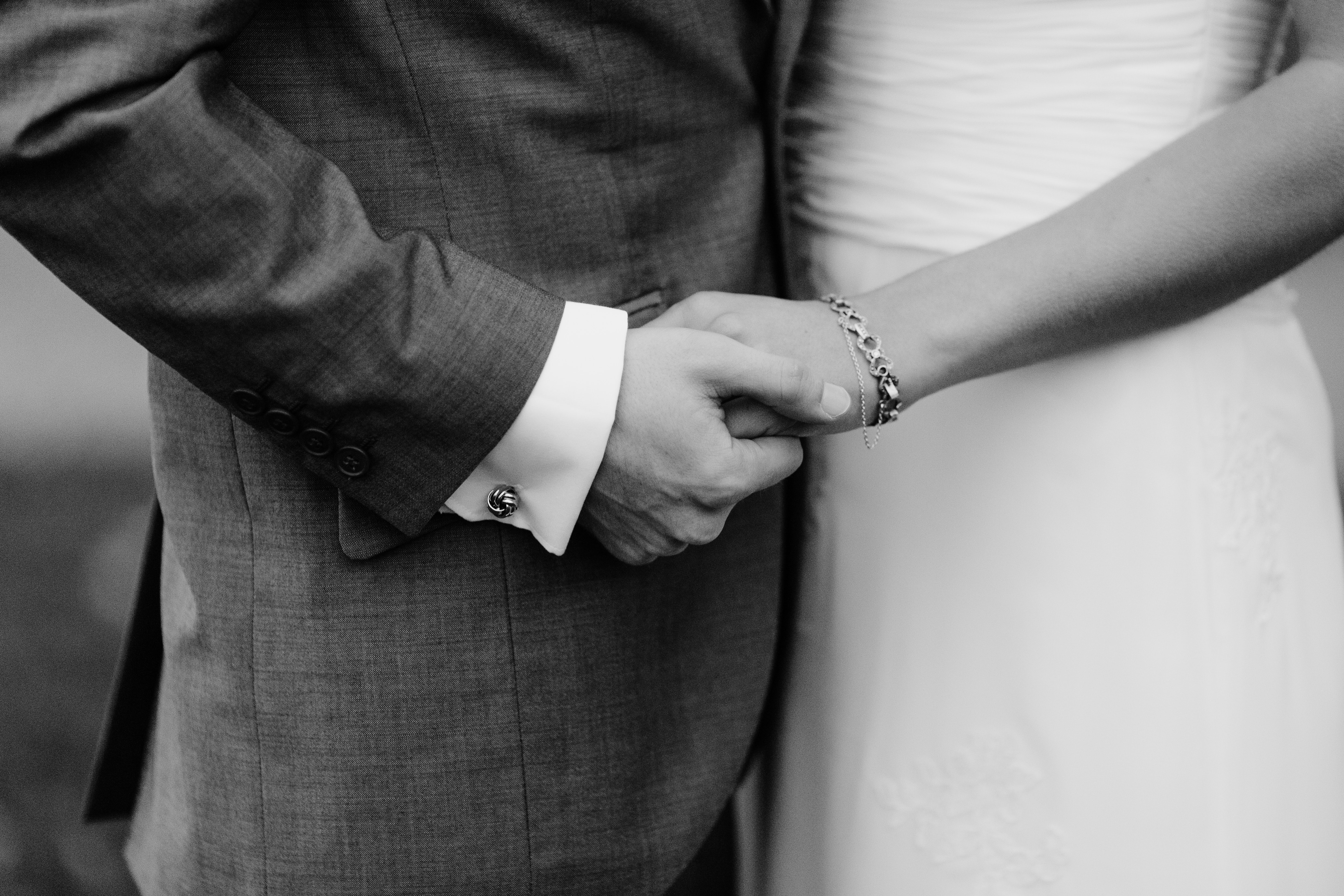 grayscale photo of man and woman holding each others hands