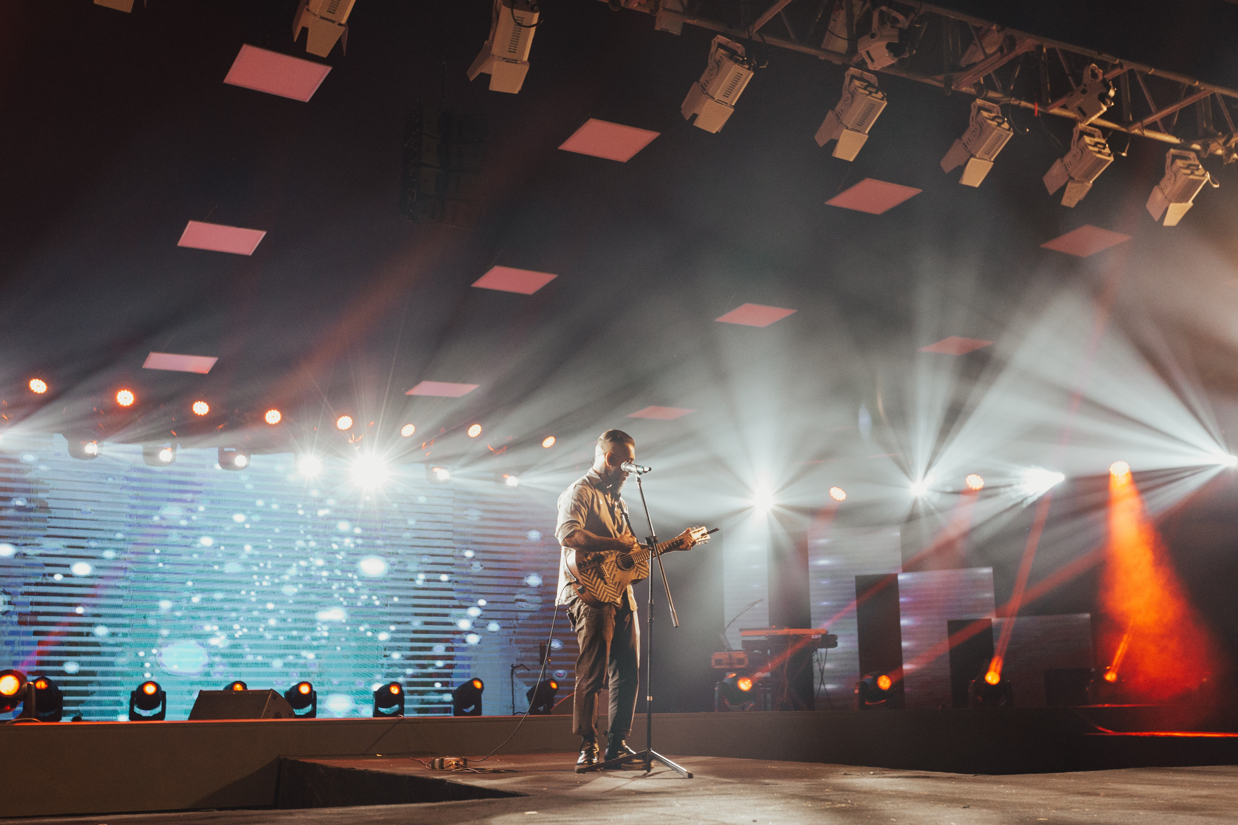 man standing on stage playing guitar