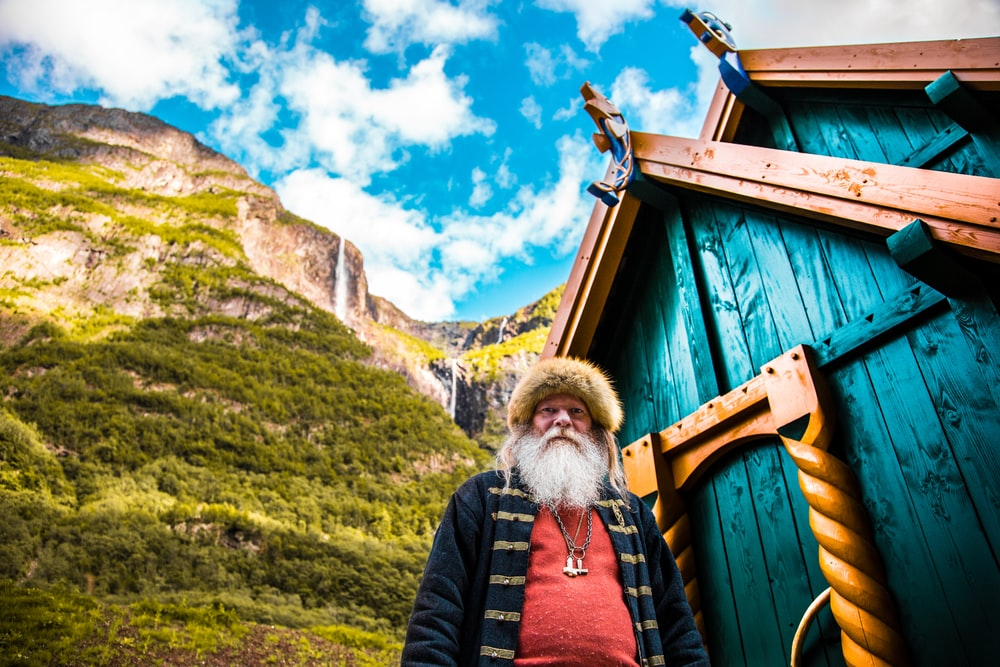 worm's eye view photography of man in front of green wooden shed