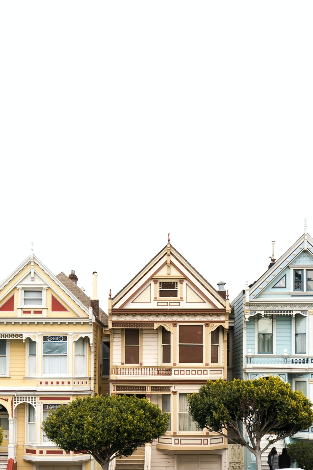 three assorted-color houses under white clouds