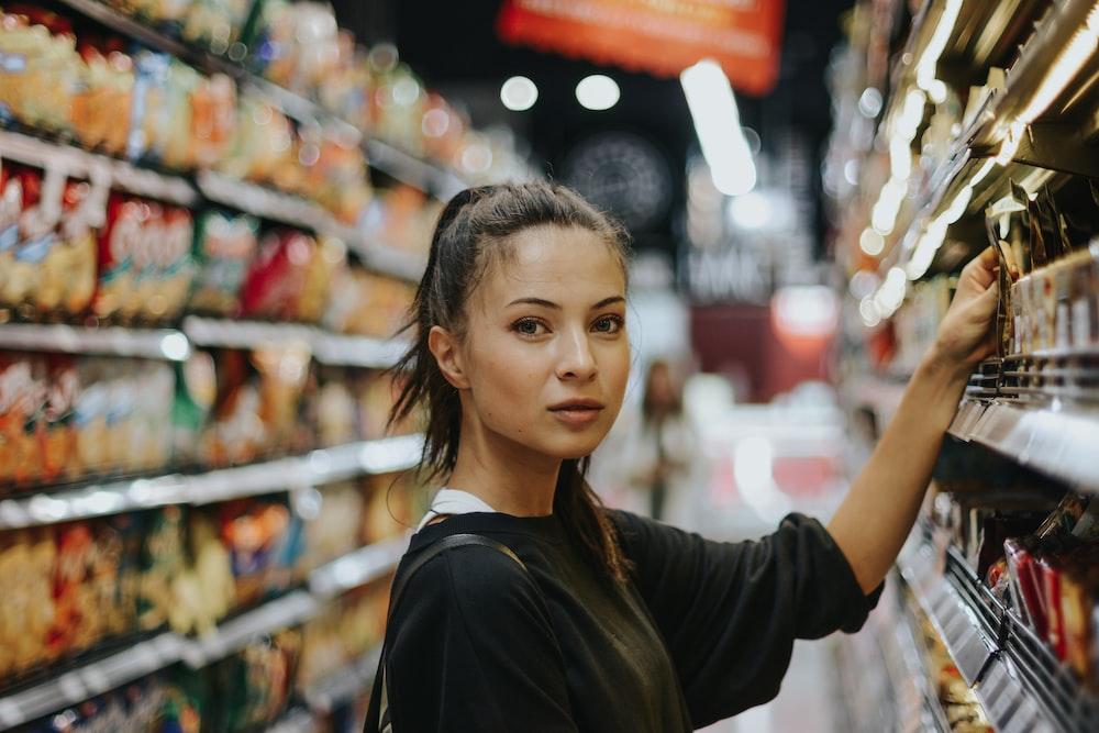 woman selecting packed food on gondola