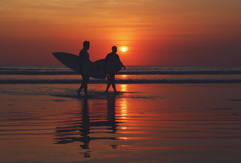silhouette of two people walking on seashore during sunset