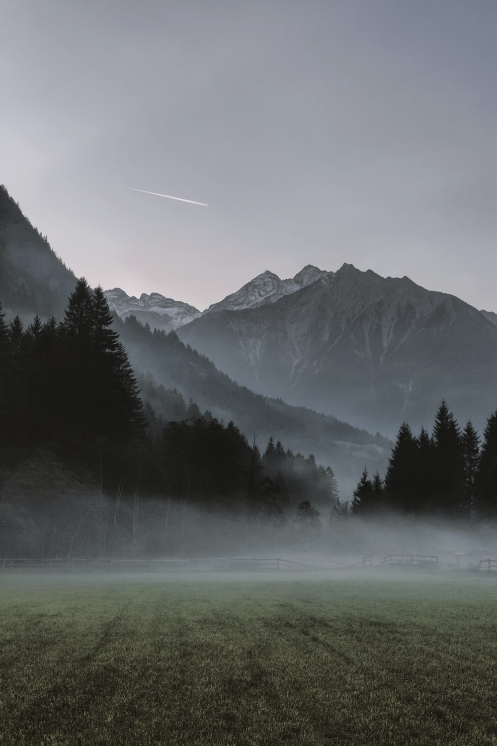 landscape photo of mountains covered by fogs and view of contrail