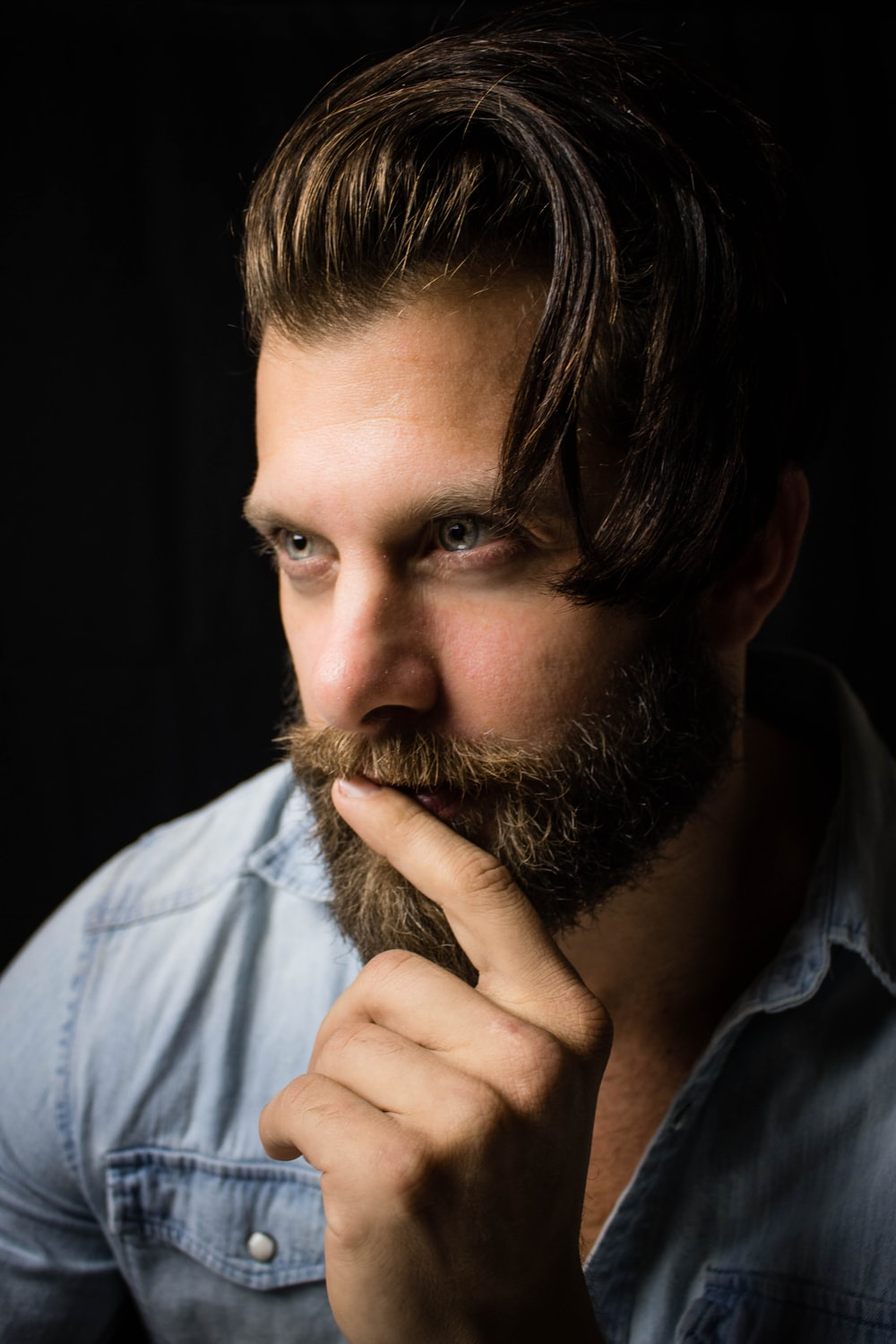 man with index finger on lips