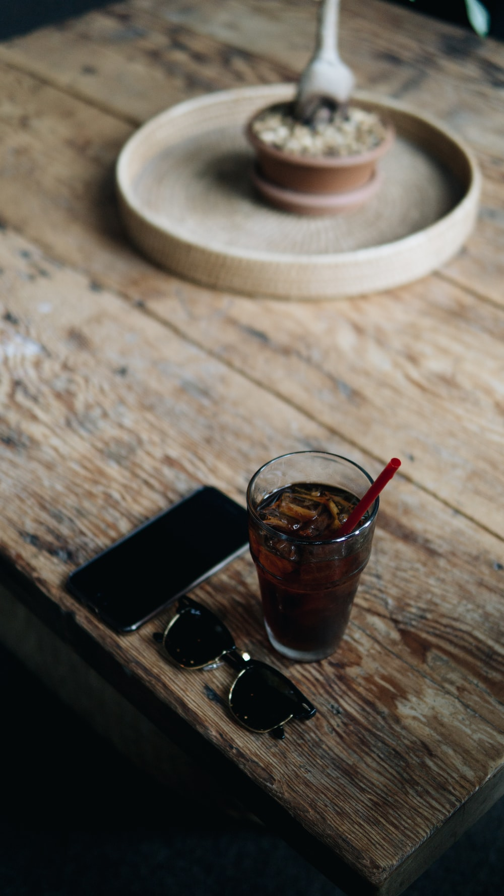 clear drinking glass beside black smartphone on brown wooden table