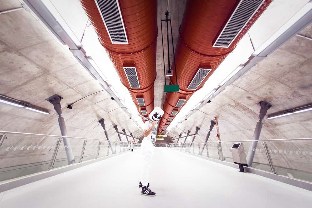 man standing under brown tunnel