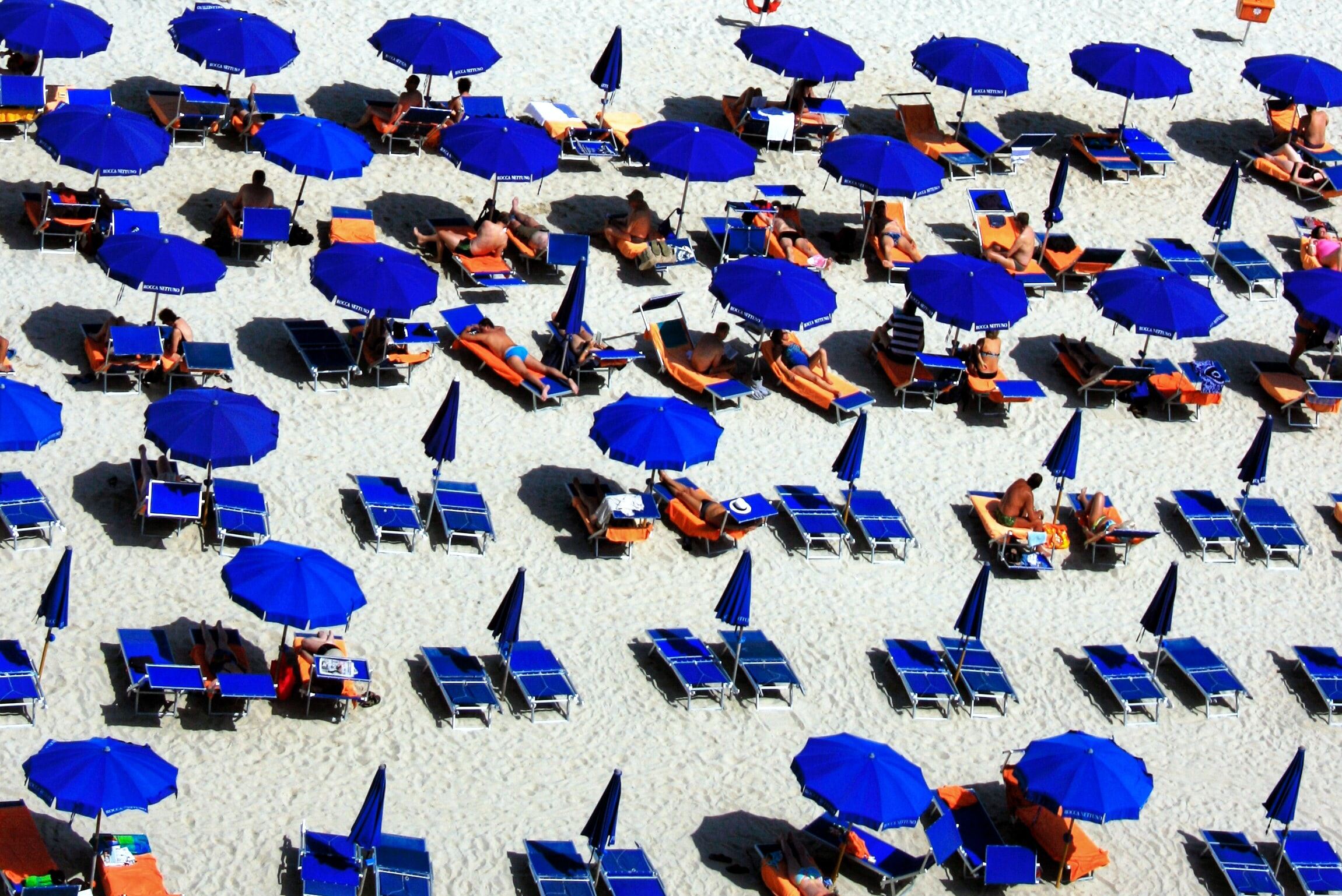 aerial photo of beach lounge chairs and umbrellas