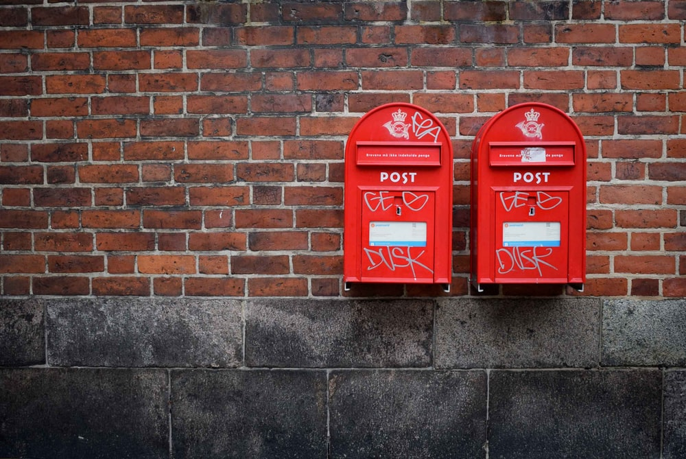 photo of two red post boxes mounted in brown concrete wall