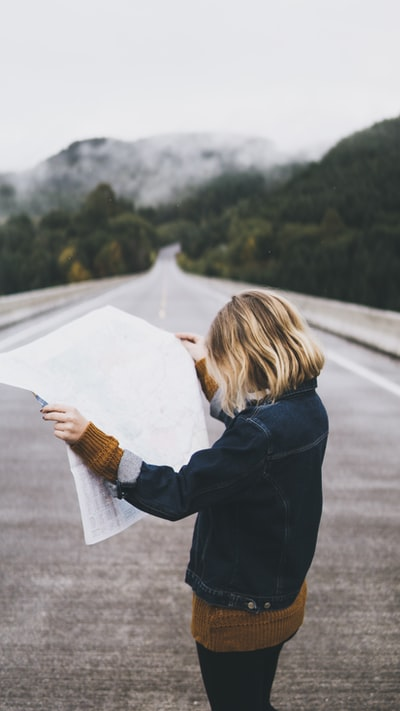 woman looking at map while standing on road