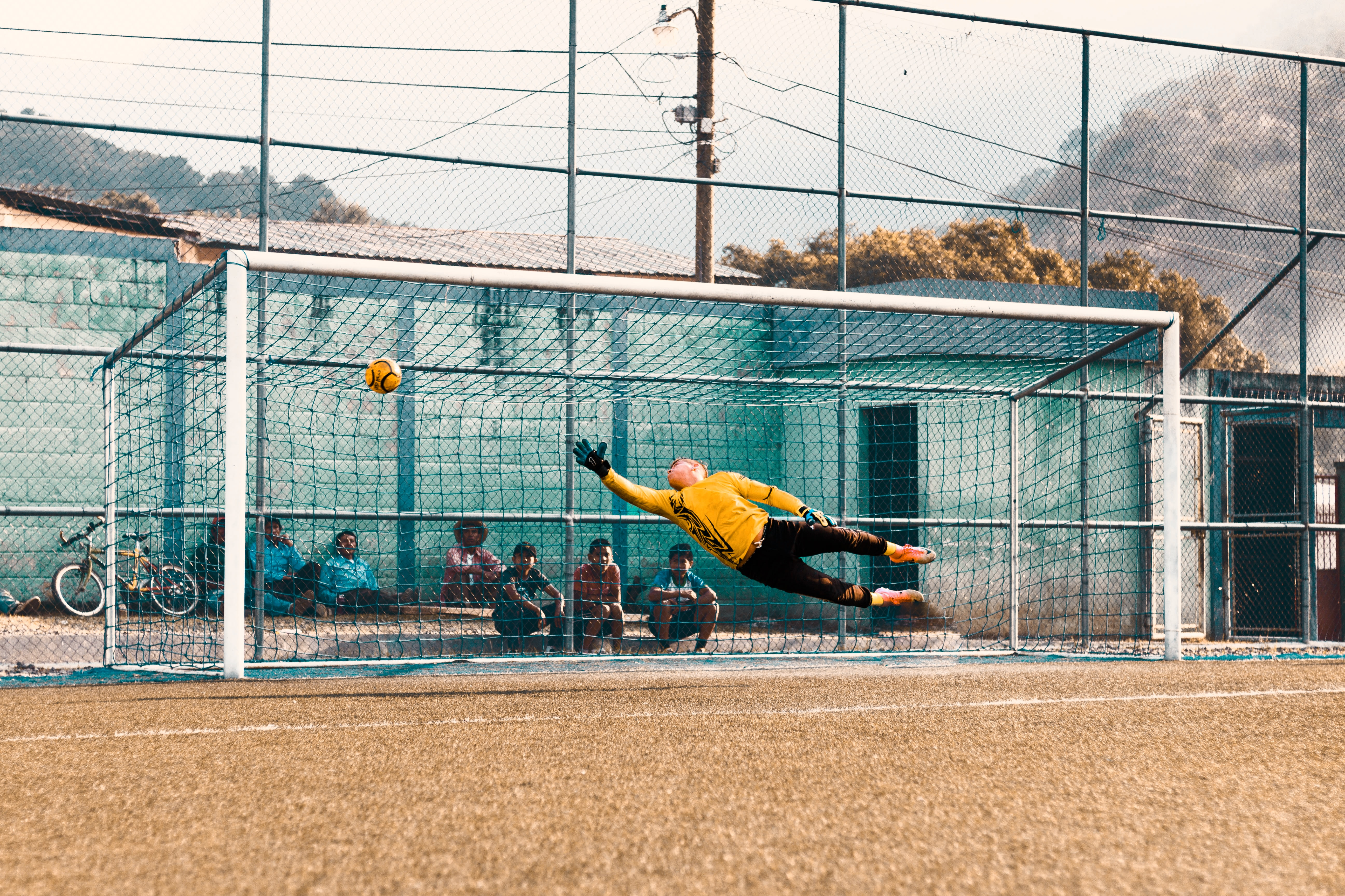 man jump about to hold ball near net