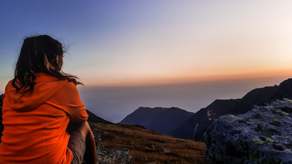 woman facing mountain during golden hour