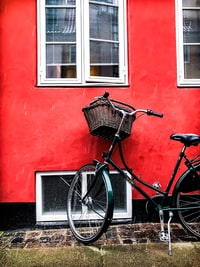 black cruiser bicycle beside red wall