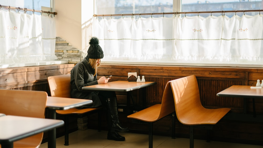 person sitting in front of brown wooden table