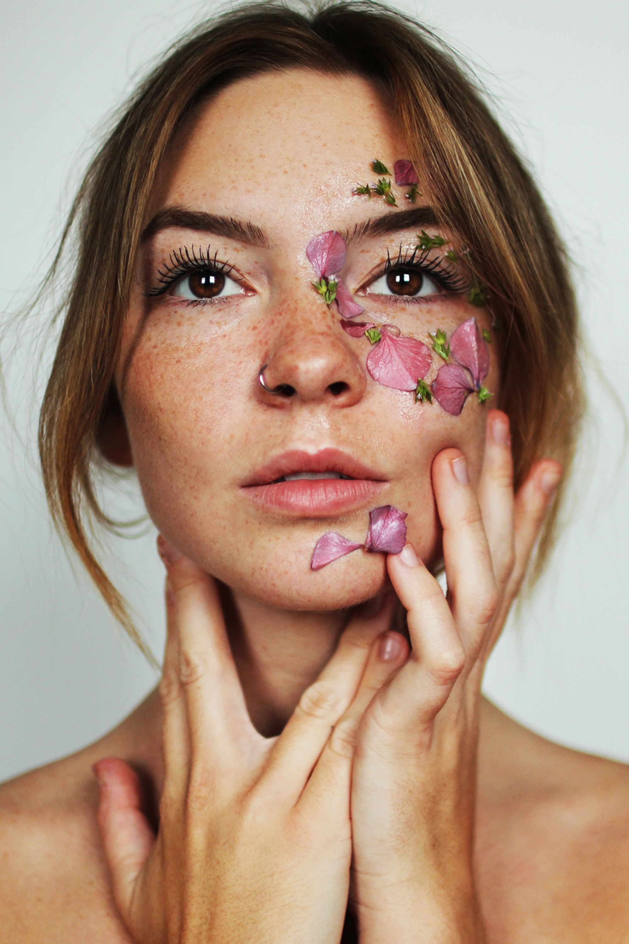woman's face with pink flower petals on her face