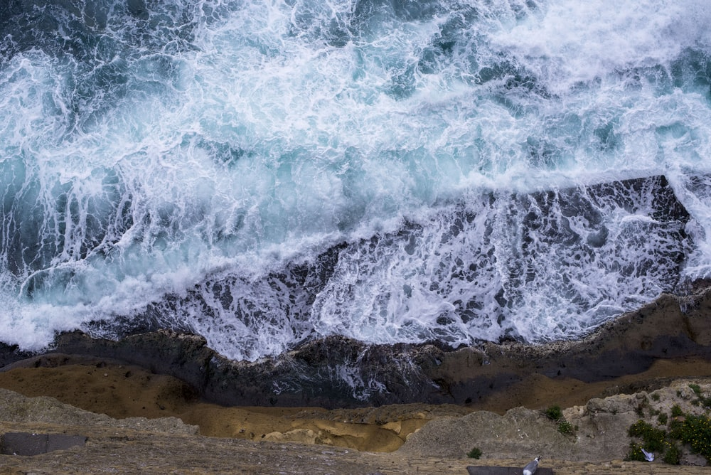 aerial view of waves crushing against rocks