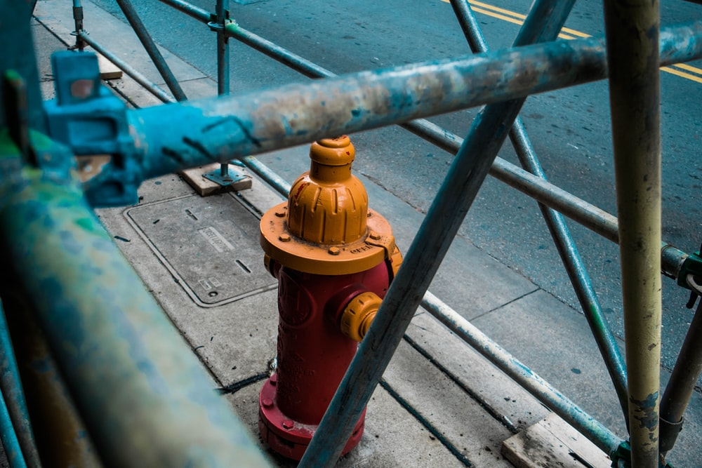 closeup photo of orange fire hydrant covered with metal rack
