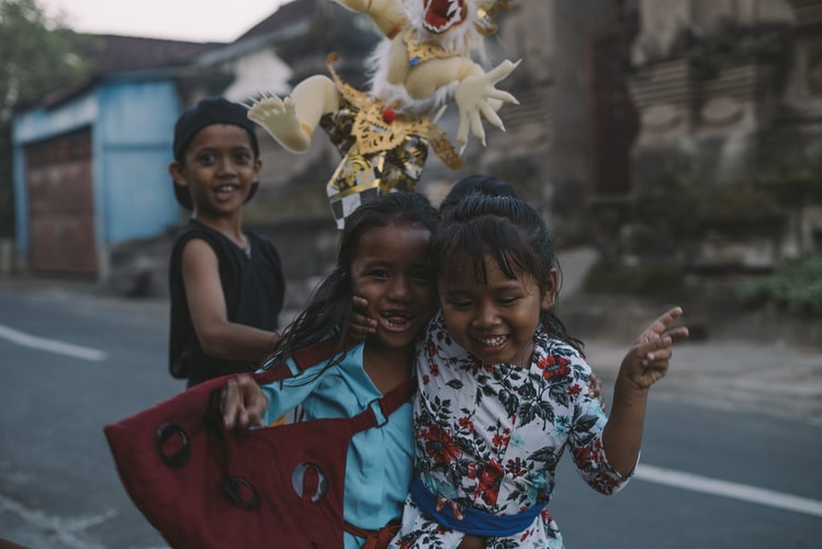 A photo of two girls hugging each other and looking at the camera while a boy behind them is holding some flowers. They are children, it is innocent and joyous.