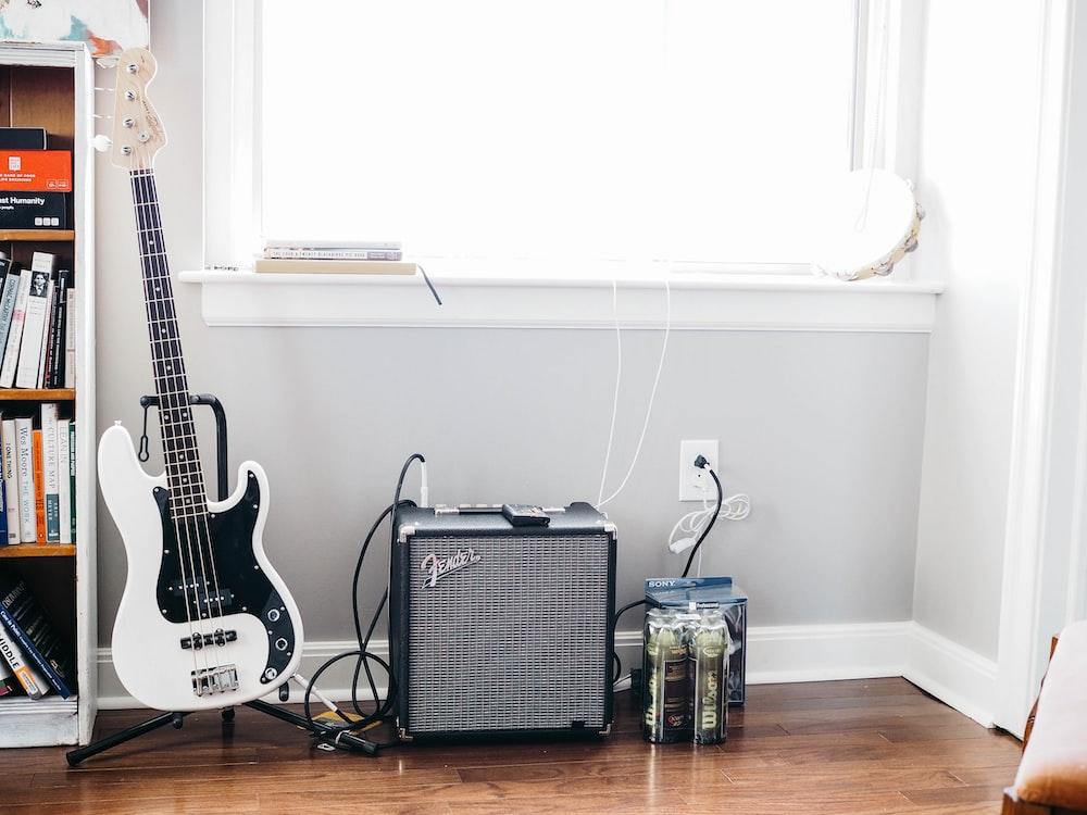 white and black stratocaster guitar on black guitar stand beside black Fender guitar amplifier