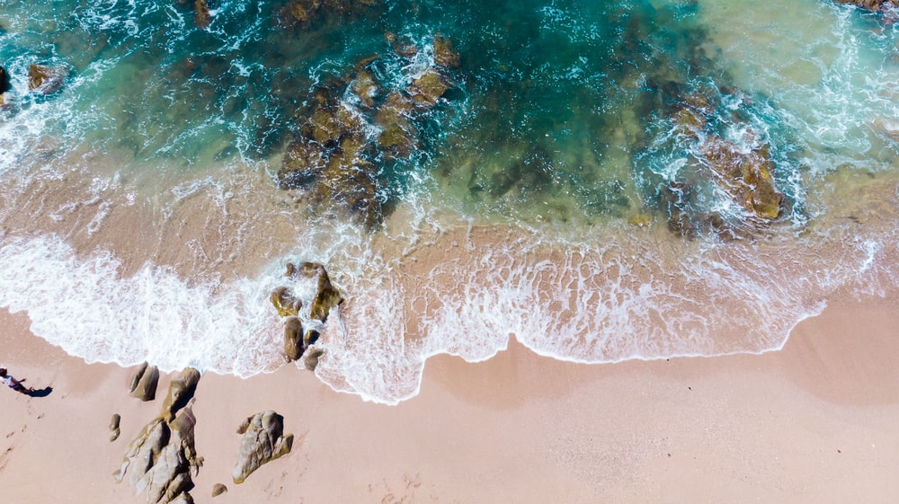 photo of sea waves crushing rocks