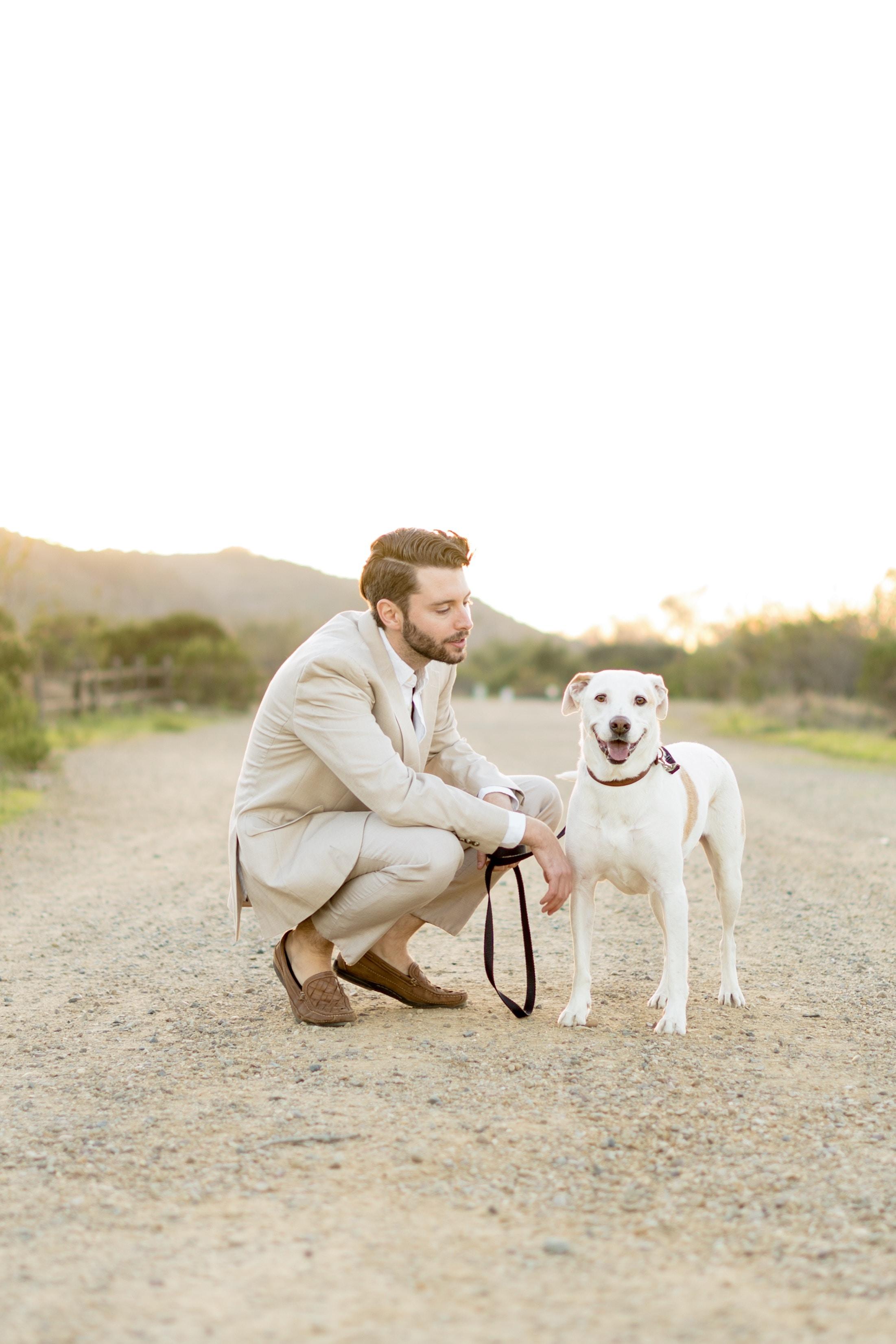 man sitting beside dog at dirt road