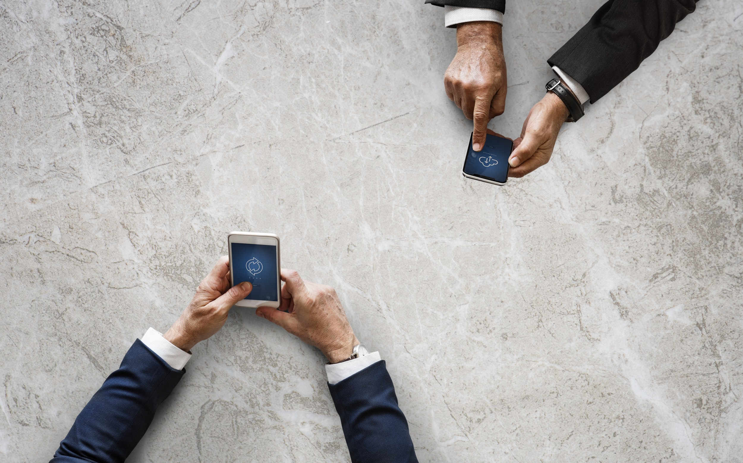 two person's holding smartphones