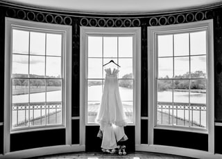 grayscale photo of gown hanged on window