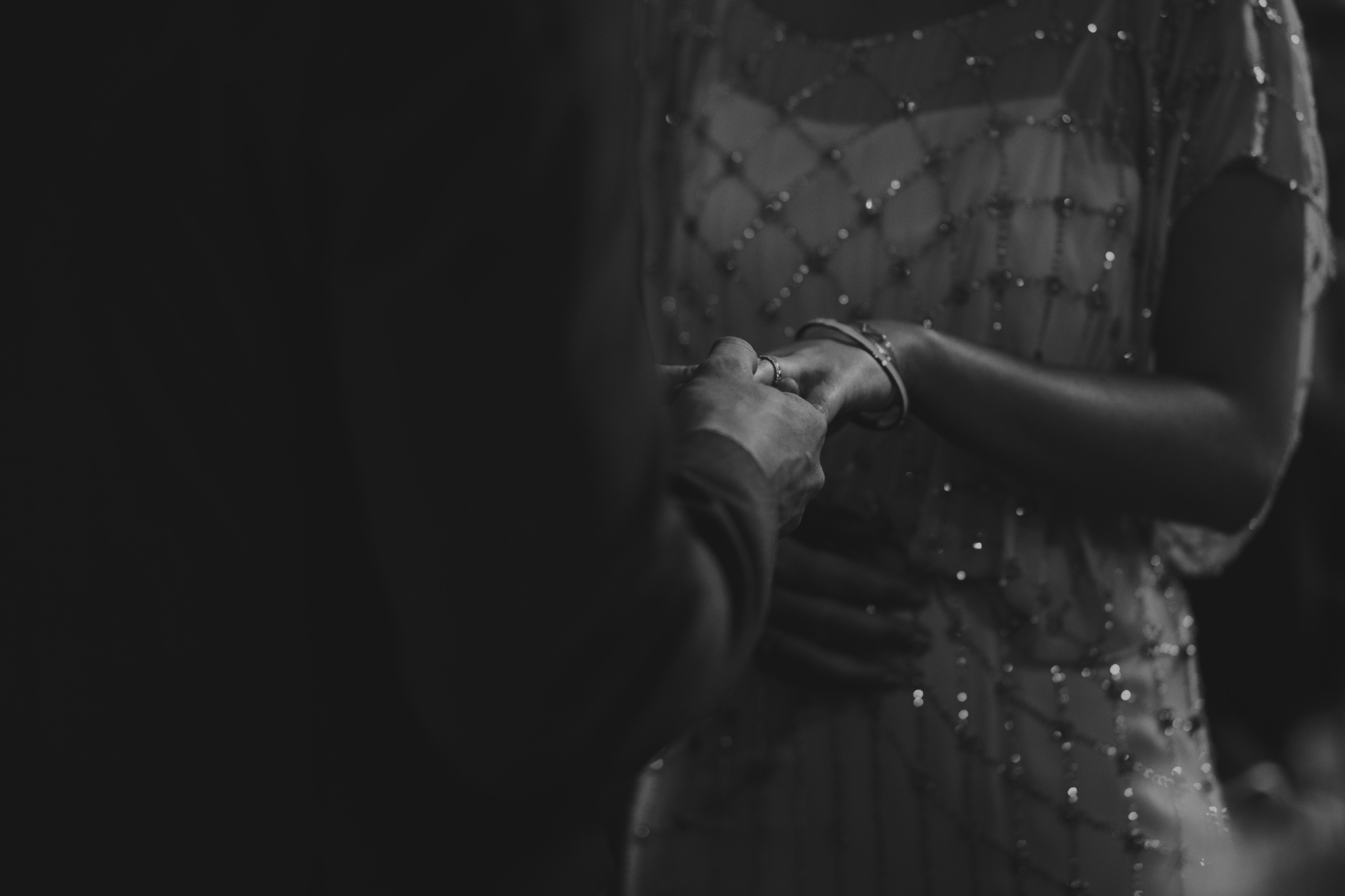 grayscale photo of woman holding man's hand