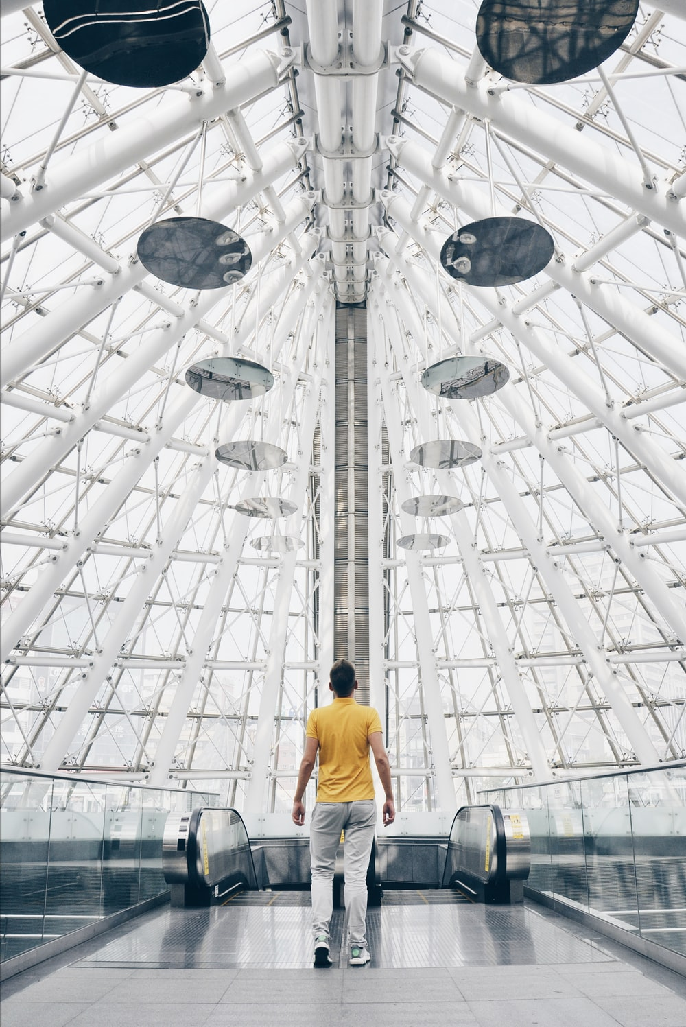 man standing under glass panel dome during daytime