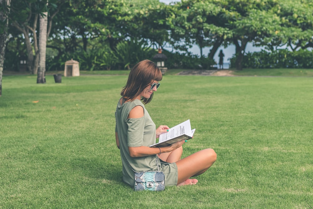 woman sitting on green grass while reading book