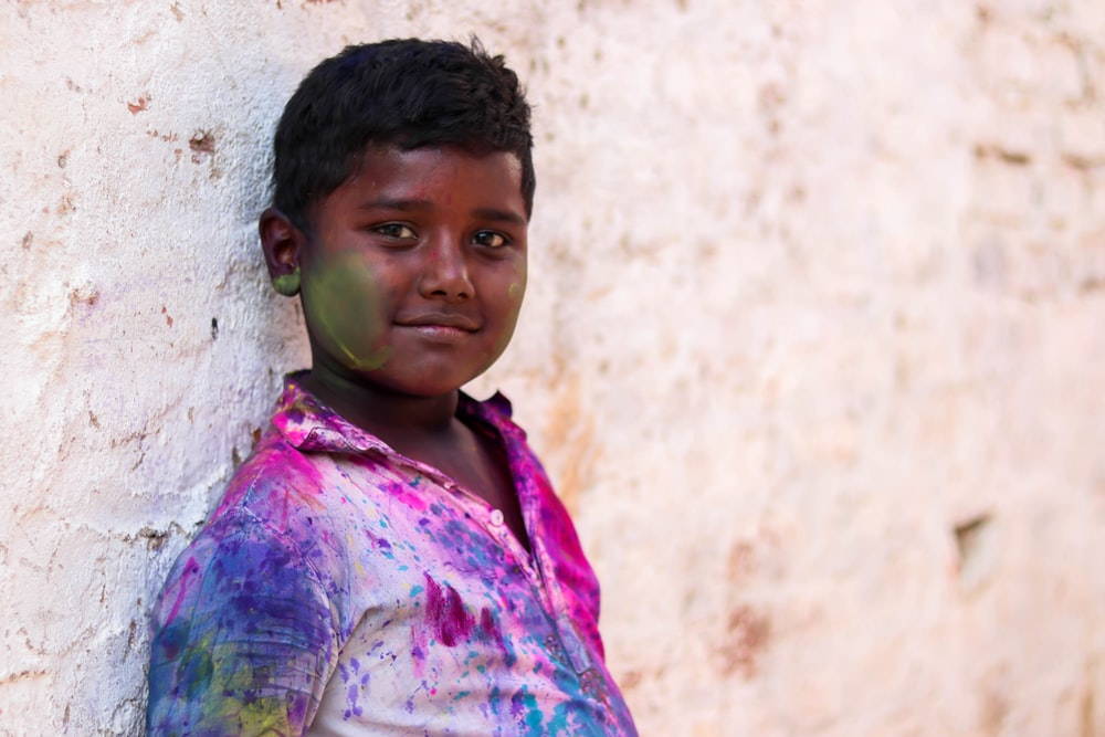 boy leaning on white wall at daytime