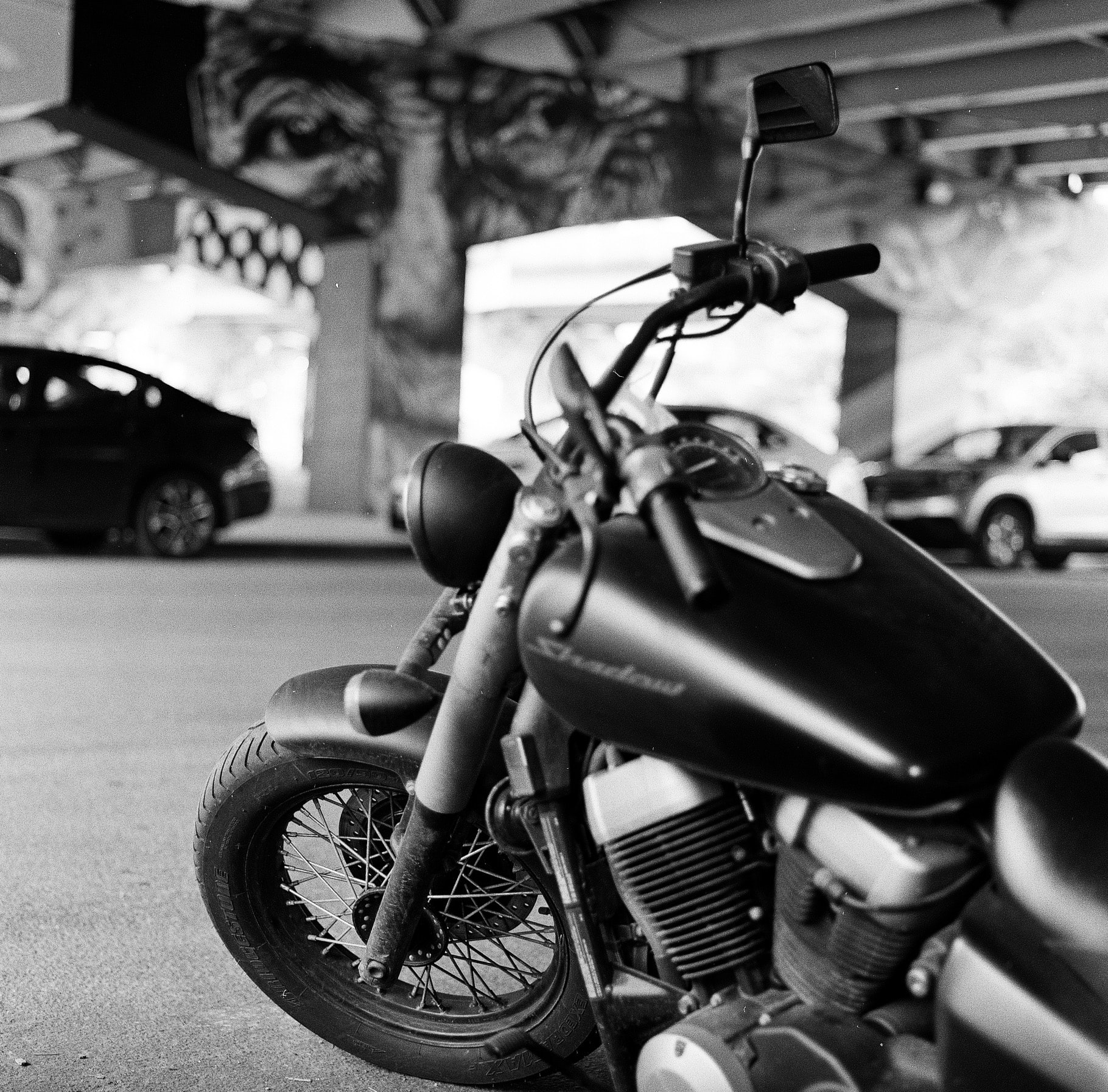 grayscale photography of standard motorcycle under bridge
