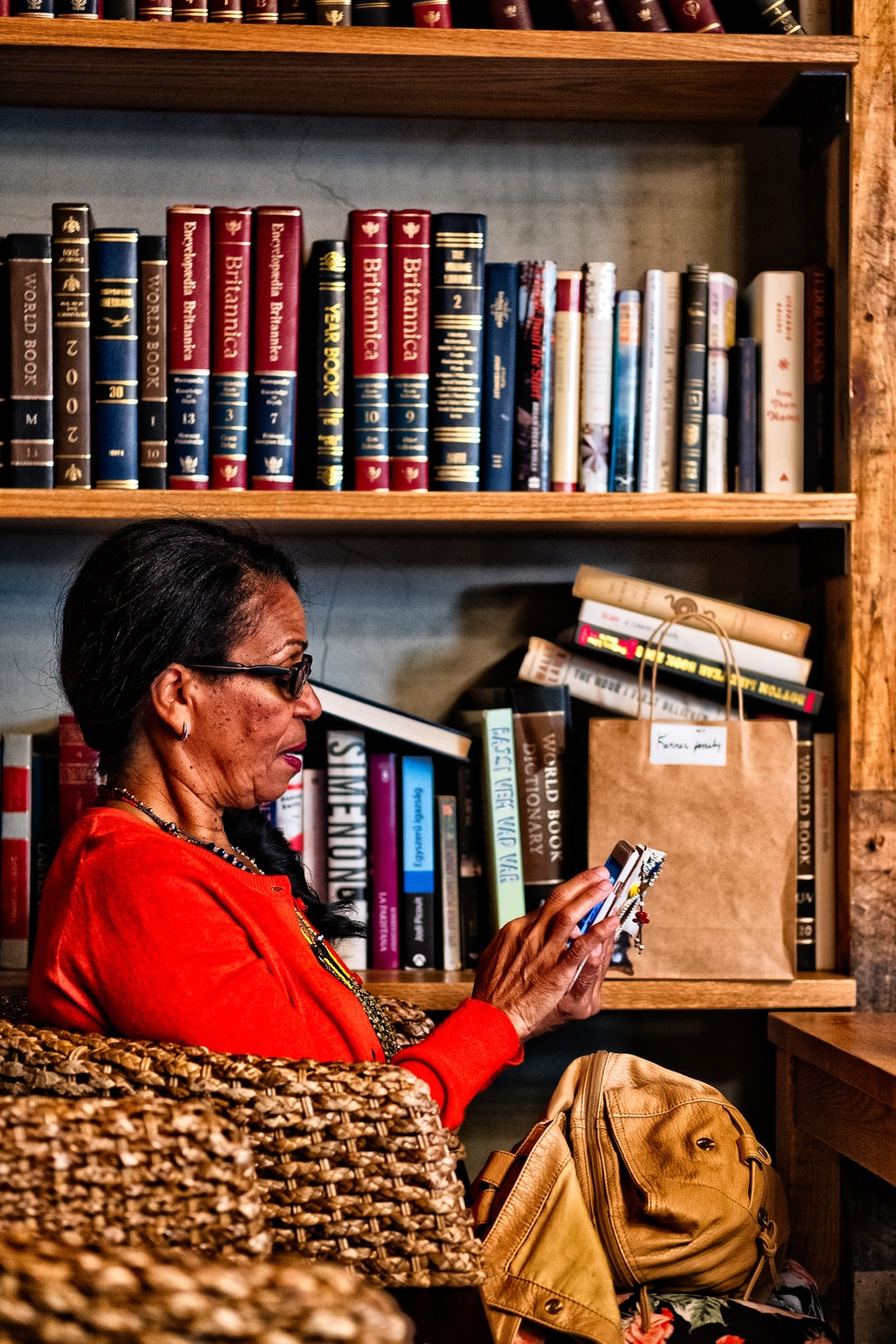 woman sitting on chair using Android smartphone near bookshelf